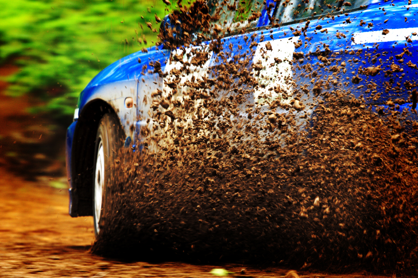 A car sprays mud as it zips around a corner in a dirt road rally